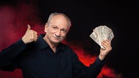 Alter Mann mit Dollarscheinen stockbilder