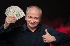 Alter Mann mit Dollarscheinen Stockfotos