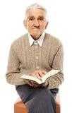 Alter Mann mit einem Buch stockfotografie