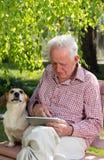 Alter Mann mit Hund und Tablette im Garten Stockfotografie