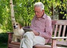 Alter Mann mit Hund und Tablette im Garten Stockbilder
