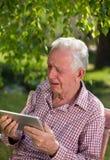 Alter Mann mit Tablette schreiend im Garten Lizenzfreies Stockfoto