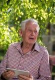 Alter Mann mit Tablette schreiend im Garten Stockbild