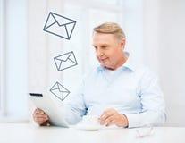 Alter Mann mit Tabletten-PC-Computer zu Hause Lizenzfreie Stockbilder