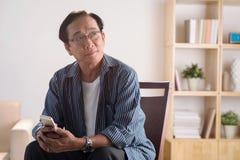 Alter Mann mit Telefon stockbilder