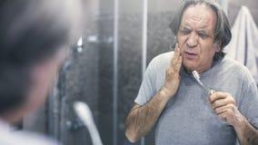 Alter Mann mit Zahnschmerzen vor Spiegel stockfotografie