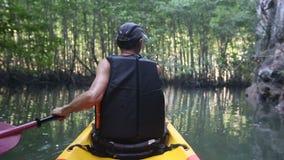 alter Mann schaufelt auf Kajak in der Schlucht unter Mangrovendschungel stock video