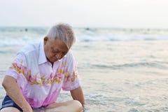Alter Mann sitzt auf dem Strand Lizenzfreie Stockfotografie