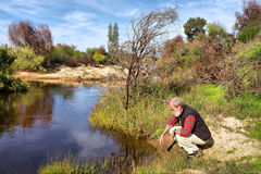 Alter Mann sitzt nahe bei Fluss in den Bergen Lizenzfreies Stockfoto