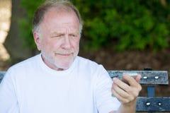 Alter Mann skeptisch von der Textnachricht lizenzfreies stockfoto