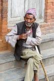 Alter Mann in traditioneller Newar-Kleidung sitzt auf Schritten Lizenzfreies Stockfoto