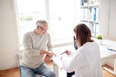 Alter Mann und Doktor mit Verordnung am Krankenhaus Stockbild