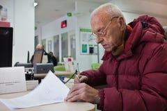 Alter Mann unterzeichnet Dokumente in Bank Stockfoto