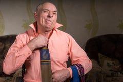 Alter Mann versucht auf einer Bindung mit unbefriedigtem Gesicht Lizenzfreies Stockbild
