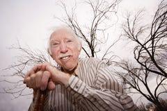 Alter Mann vor bloßen Bäumen Stockbild