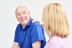 Alter Mann wird unterstützt, indem man Assistenten pflegt stockfoto