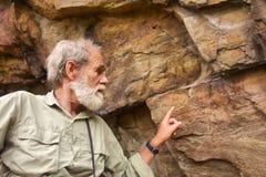 Alter Mann zeigt auf die alten Buschmannmalereien Lizenzfreies Stockfoto