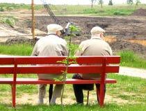 Alter Mann zwei, der auf der Bank sitzt Stockfoto