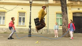 Alter Manntau, der mit drei Mädchen überspringt stock video