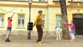 Alter Manntau, der mit drei Mädchen überspringt stock video footage