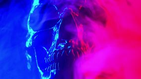Alter menschlicher Schädelkopf, der in Rauchnahaufnahme sich dreht Neontürkis und rotes Licht Gespenstisch und unheimlich Zauber, stock video footage