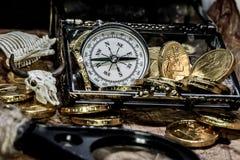 Alter Messingkompaß, der voll auf einer sehr alten Karte mit Schatzkasten der goldenen Münzen, des Schädels und des Messers liegt stockbild