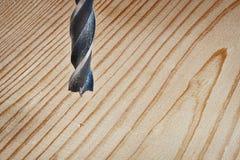 Alter Metallbohrer und hölzerne Kiefernplanke Stockfoto