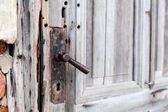 Alter Metallgriff in einer Holztür r stockbild