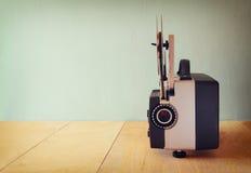 Alter 8mm Film-Projektor über Holztisch und strukturiertem Hintergrund Stockfoto