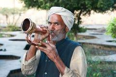 Alter moslemischer Mann mit dem Turban, der eine Trompete durchbrennt Lizenzfreies Stockbild