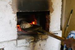 Alter Ofen mit Flammenfeuer und -brot Lizenzfreie Stockfotos