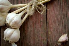 Alter organischer Knoblauch ganz und Nelken auf dem hölzernen Hintergrund Stockfoto