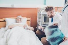 Alter Patient sagt zu den roten bärtigen Jungen Doc. seinen symptomes, h stockfoto