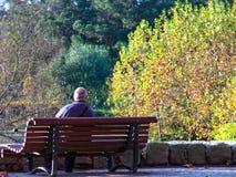 Alter pensionierter Mann in einer Bank Stockfotos