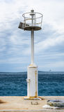 Alter Pier mit einem Leuchtturmleuchtfeuer und -ruhigen See Lizenzfreies Stockbild