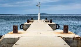 Alter Pier mit einem Leuchtturmleuchtfeuer und -ruhigen See Lizenzfreie Stockbilder