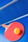 Alter Pingpongschläger und ein eingebeulter Ball auf blauer Pingpongtabelle stockbild