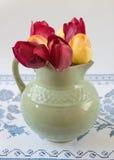 Alter Pitcher mit Blumen von Tulpen Lizenzfreie Stockfotos
