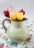Alter Pitcher mit Blumen von Tulpen Stockbilder