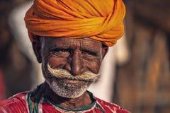 Alter Rajasthani-Mann vor dem hintergrund seiner Kamele Lizenzfreies Stockfoto