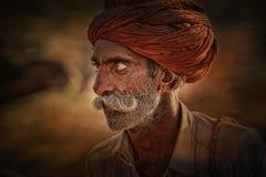 Alter Rajasthani-Mann vor dem hintergrund seiner Kamele Stockbild