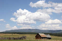 Alter Ranch-Blockhaus-Bretterzaun Cumulus White Clouds Stockbilder