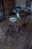 Alter Raum mit Tabelle, Stühlen und einer Babywiege Lizenzfreies Stockbild