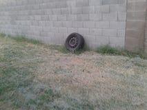 Alter Reifen, der oben an einer grauen Backsteinmauer sich lehnt Stockfotos