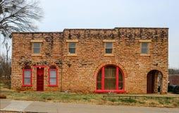 Alter Retro- Backsteinbau mit gewölbten Fenstern mit Rot malte Holzarbeit unter einem Winterhimmel nahe Route 66 in Oklahoma lizenzfreie stockfotografie