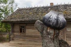 Alter Roheisentopf, der an einem Baum auf einem Hintergrund eines Dorfhauses für Druck hängt stockbilder