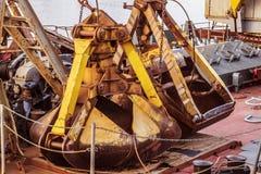 Alter rostiger Baggereimer, der auf der Plattform eines Flussschiffs liegt Lizenzfreie Stockfotos