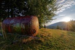 Alter, rostiger Behälter auf Wiese, Sonnenaufgang über den Bergen und Wald Stockbild
