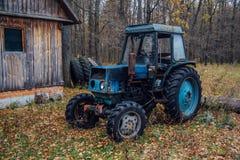 Alter rostiger blauer Traktor in einem Holz Russisches Dorf Stockbild