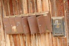 Alter rostiger Briefkasten auf einem Bretterzaun Stockbilder